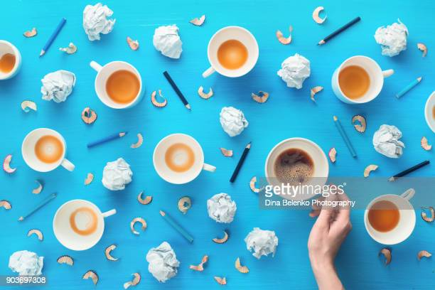 hand holding a coffee cup in a creative profession workplace. top view coffee pattern with crumpled paper balls and pencils. generating ideas and brainstorm concept. - food journal stock-fotos und bilder