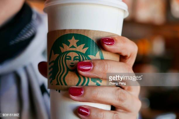 Hand holding a coffee cup in a Starbucks coffee shop In 2017 the revenue of Starbucks China rose by 30% and till 2021 the total amount of Starbucks...