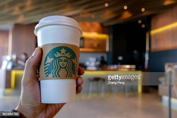 Hand holding a coffee cup in a Starbucks coffee shop Since January 1st Starbucks took back the management rights of more than 1300 stores in East...