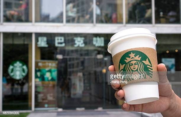 Hand holding a coffee cup outside a Starbucks shop in Beijing Jianwai Soho Starbucks reported a higherthanexpected revenue and 7 percent global...