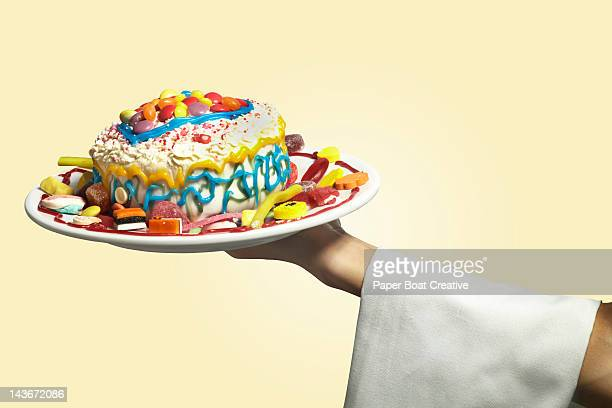 hand holding a colorful messy home made cake - 不完全な美しさ ストックフォトと画像
