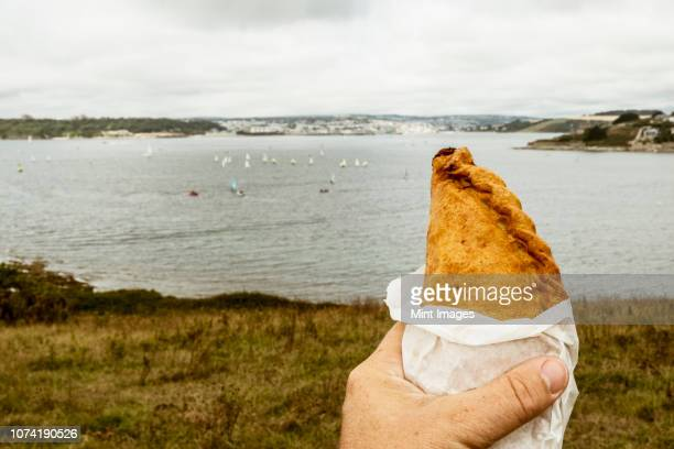a hand holding a cornish pasty baked pastry with a crimped edge, seated overlooking a sea estuary. - cornish pasty stock-fotos und bilder
