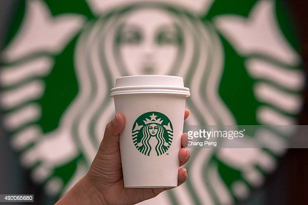 Hand holding a cup of coffee in front of Starbucks logo Starbucks is streamlining the ordering process so customers are able to get that cup of...
