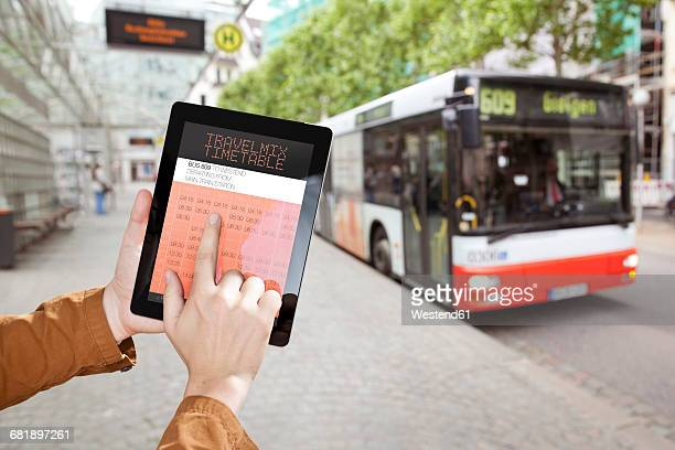 Hand holding a digital tablet with bus time table at a bus station