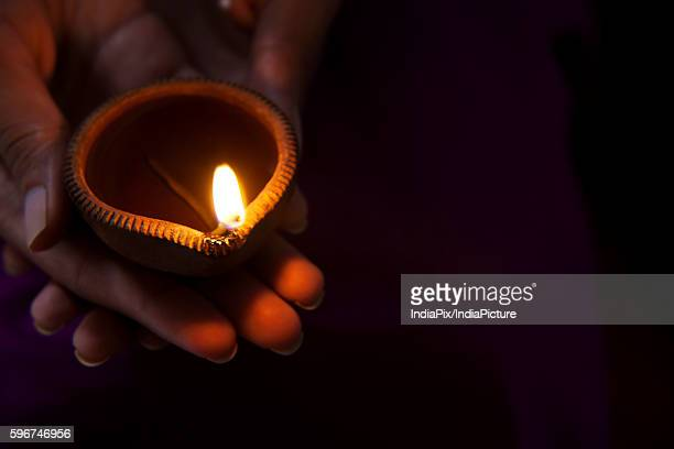 hand holding a diya - diya oil lamp stock pictures, royalty-free photos & images