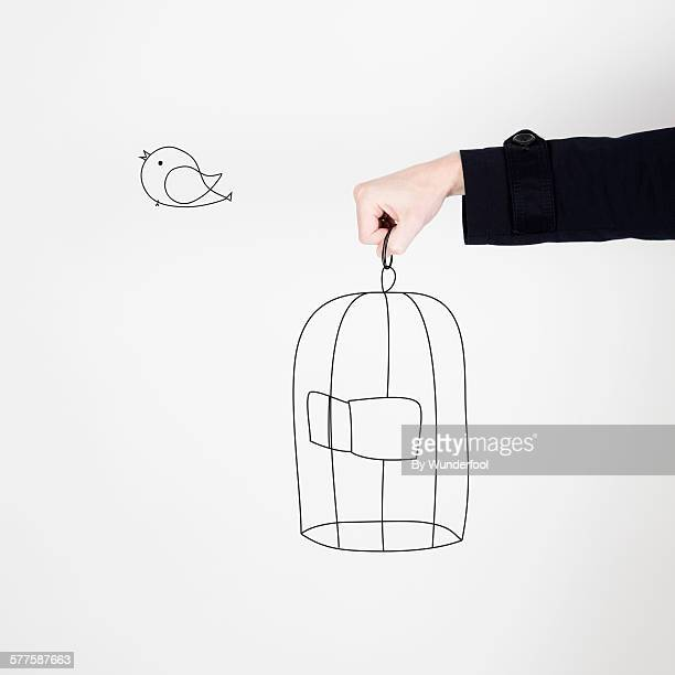 Hand holding a drawing of a birdcage