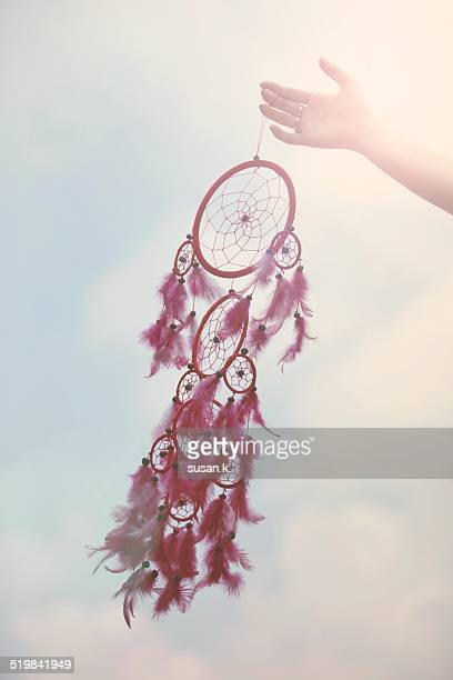 Hand holding a feathery dream catcher on blue sky