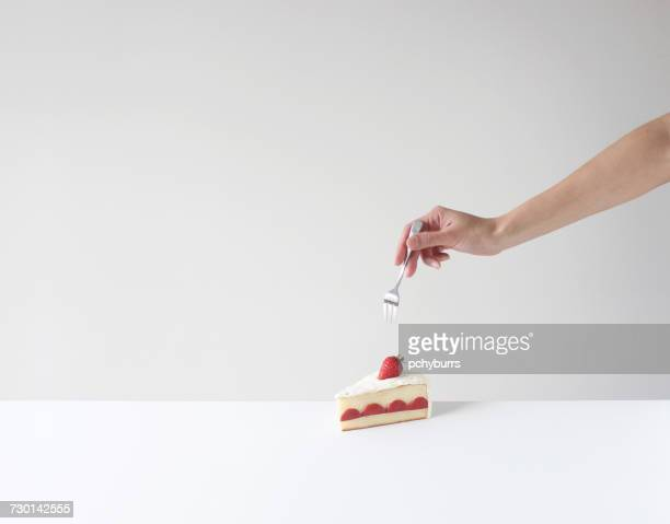 Hand holding a fork about to eat a slice of cake