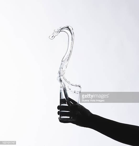 Hand holding a glass with a water splash
