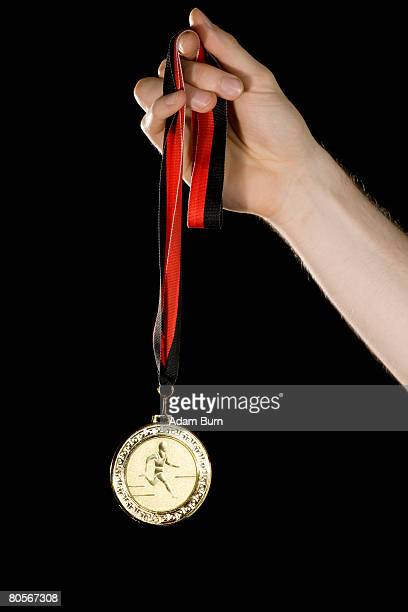 A hand holding a gold medal