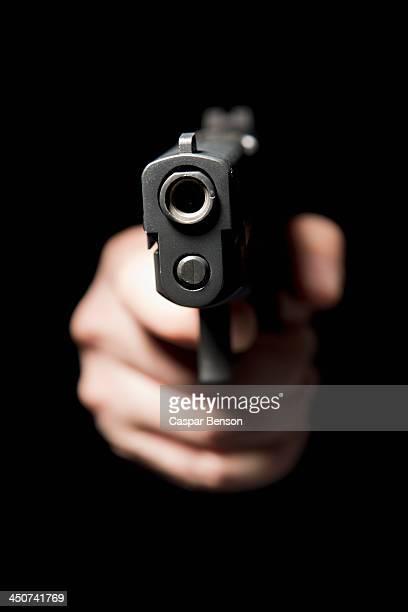 a hand holding a gun and pointing it at the camera, black background - revólver - fotografias e filmes do acervo