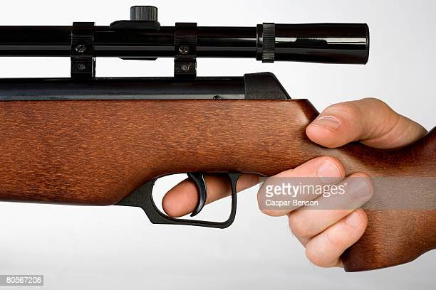 a hand holding a gun - trigger stock photos and pictures