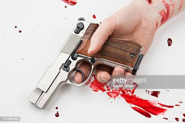 A Hand Holding A Gun Splattered With Blood