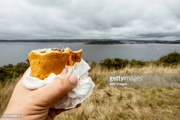 a hand holding a half eaten cornish pasty. - cornish pasty stock-fotos und bilder