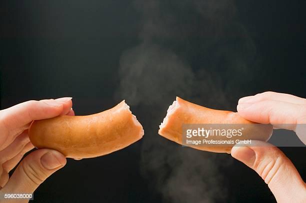 Hand holding a halved frankfurter