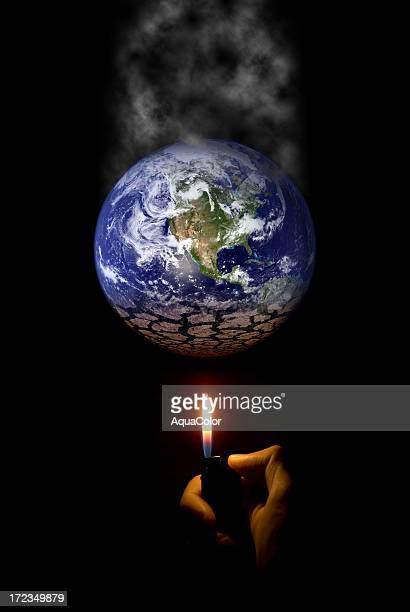 hand holding a lighter under a globe showing global warming - smoking crack stock photos and pictures