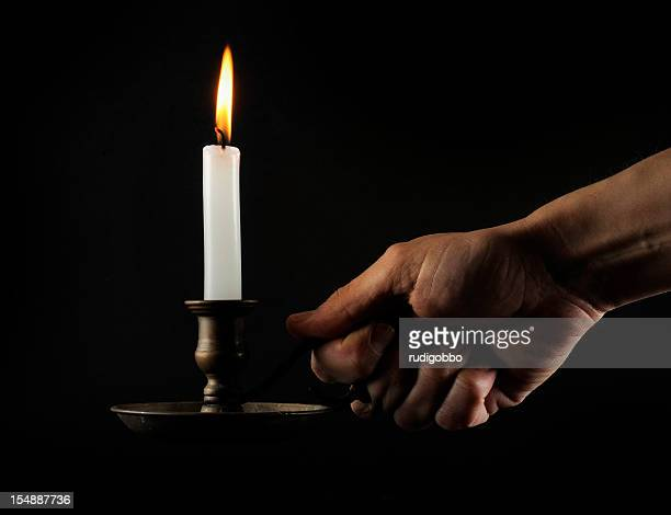Hand holding a lit candle in the dark