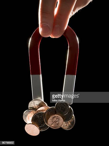 hand holding a magnet with a bunch of coins stuck to it - horseshoe magnet stock pictures, royalty-free photos & images