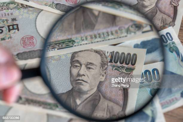 Hand holding a magnifying glass and looking into the Yen Banknotes In the early march Japan's core inflation has returned for the first time in more...