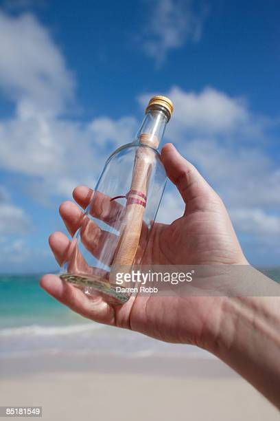 Hand holding a message-in-a-bottle on beach