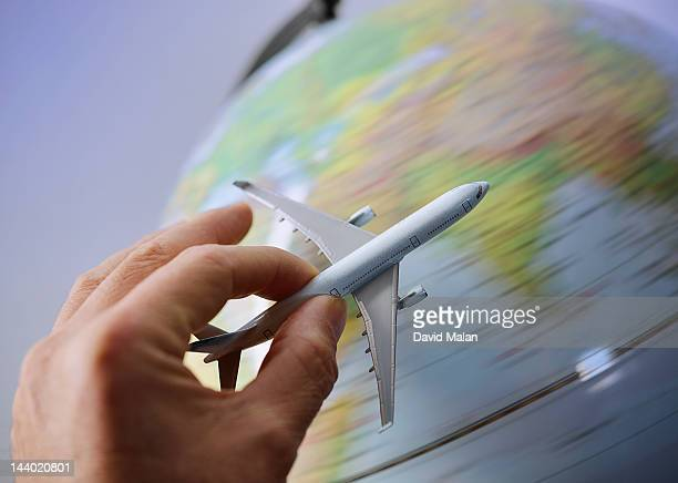 Hand holding a model plane over a spinning globe