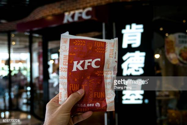 Hand holding a new KFC fried chicken snack outside a KFC restaurant Due to the slowdown in the Chinese market KFC is trying to make its brand more...