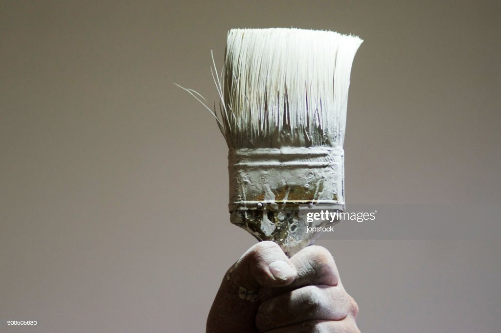 Hand holding a paintbrush with white paint : Stock Photo