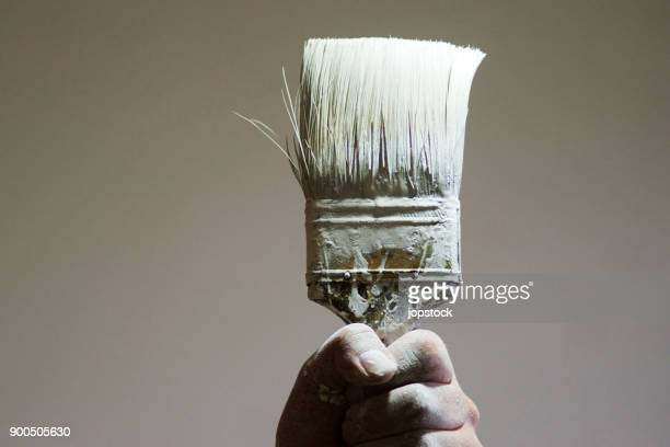 Hand holding a paintbrush with white paint