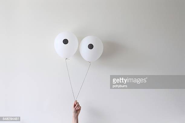 A hand holding a pair of balloons that look like eyes