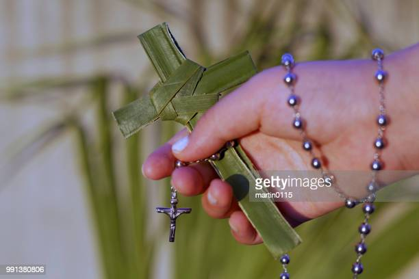 hand holding a palm cross and rosary beads
