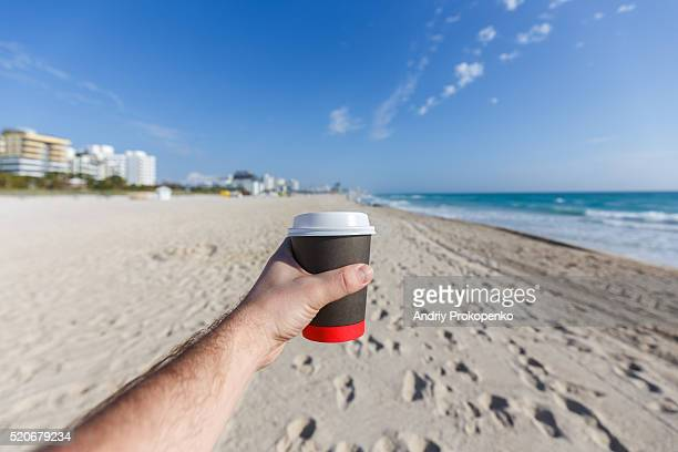 Hand holding a paper coffee cup with a beach in the background