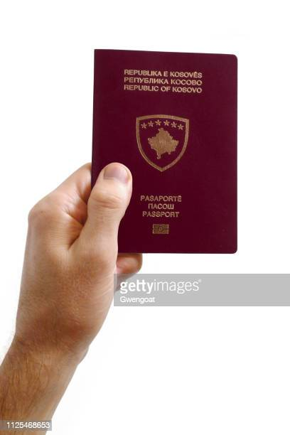 hand holding a passport from kosovo against a white background - gwengoat stock pictures, royalty-free photos & images