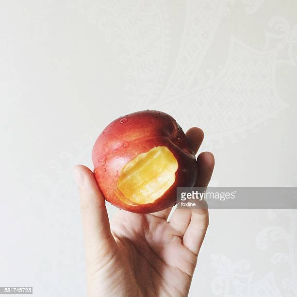 Hand holding a peach with a bite mark