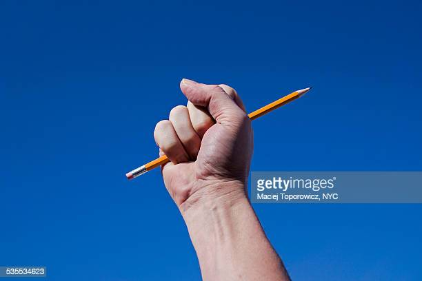 hand holding a pencil against blue sky. - extremismo imagens e fotografias de stock