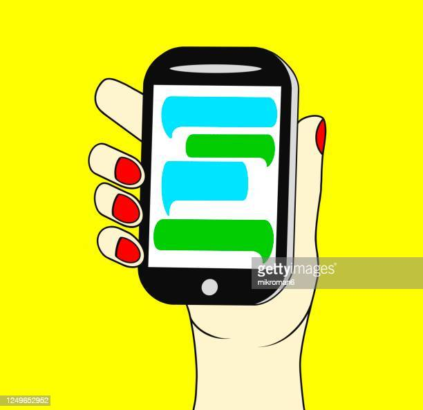 hand holding a phone with a chat speech bubbles on screen - mobile app stock pictures, royalty-free photos & images