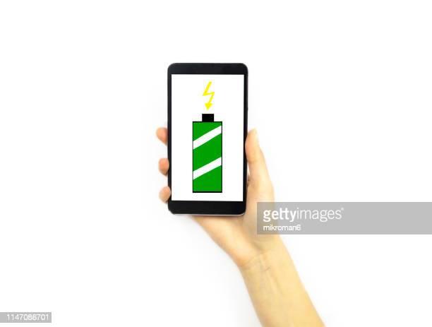 hand holding a phone with a full battery symbol - いっぱいになる ストックフォトと画像