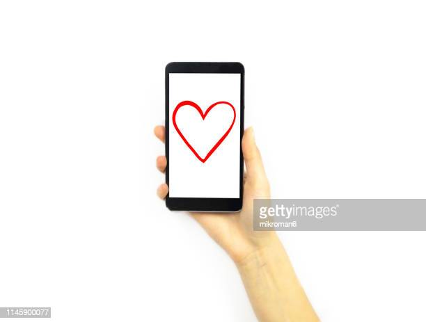 hand holding a phone with a heart on it - daten stockfoto's en -beelden