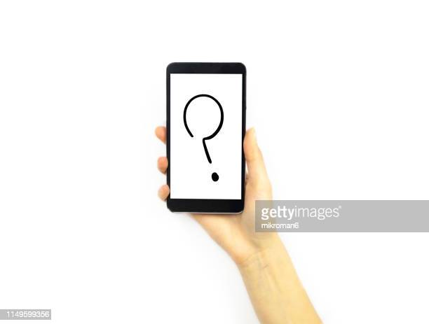 hand holding a phone with a question mark - questionnaire stock pictures, royalty-free photos & images
