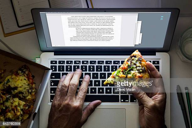 Hand holding a pizza while working on a laptop