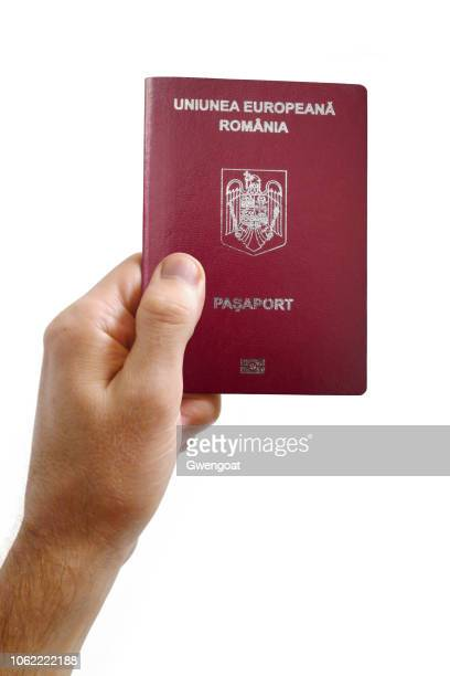 Hand holding a Romanian passport against a white background