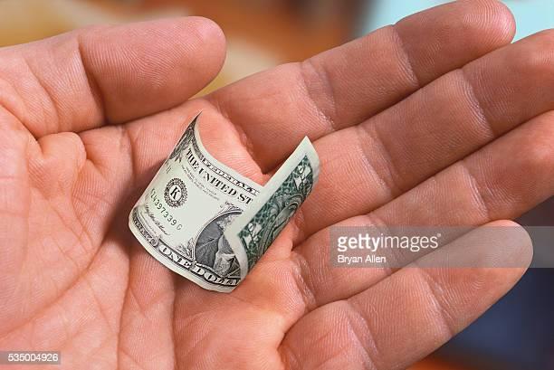 Hand Holding a Shrunken Dollar Bill