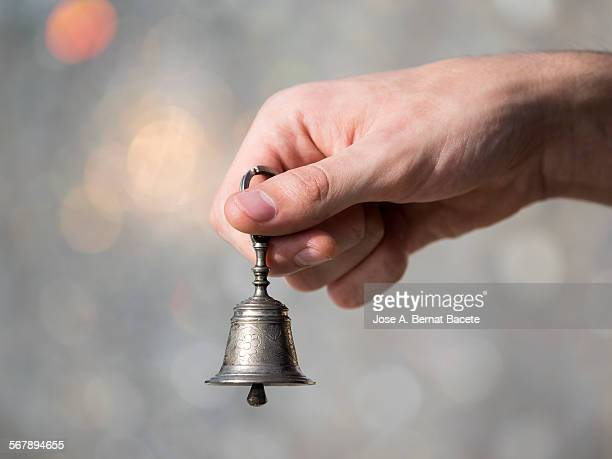 Hand holding a small bell