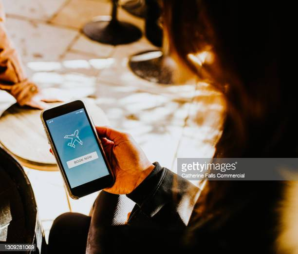 hand holding a smart phone displaying a flight booking app - flying stock pictures, royalty-free photos & images