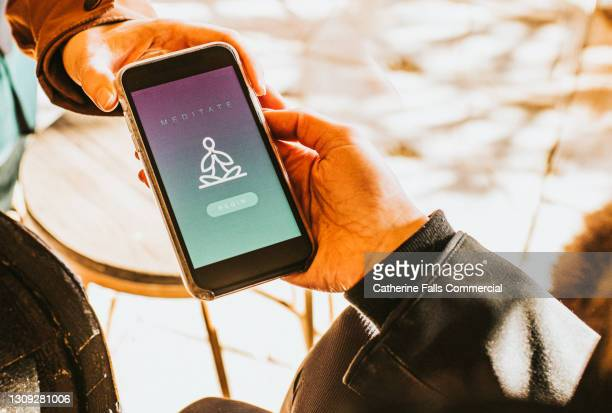 hand holding a smart phone that displays a meditation app - development stock pictures, royalty-free photos & images