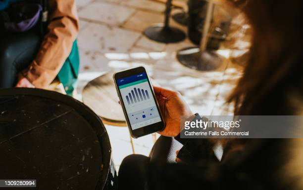 hand holding a smart phone which displays a media player app - big tech stock pictures, royalty-free photos & images