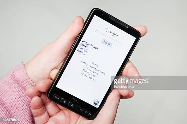 main tenant un smarthphone avec google.com applications - moteur de recherche photos et images de collection