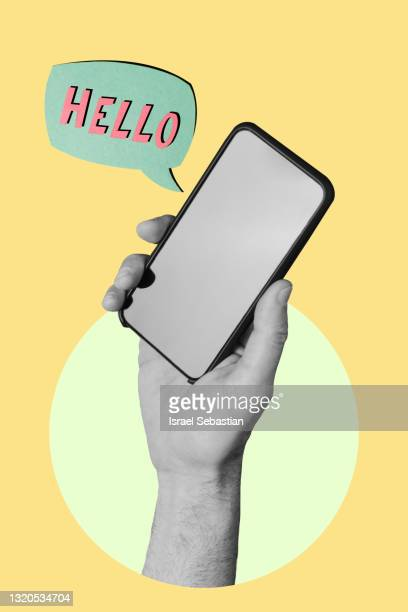 """hand holding a smartphone on yellow background while a sign appears with """"hello"""" words. - touching stock pictures, royalty-free photos & images"""