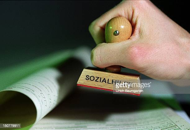 Hand holding a stamp with label ' Sozialhilfe ' over a form
