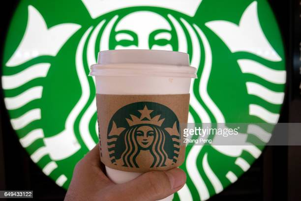 Hand holding a Starbucks coffee cup before the light box of Starbucks Siren Starbucks is growing fast in China and aims to double its locations there...