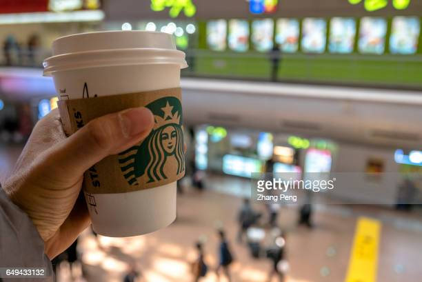 Hand holding a Starbucks coffee cup in a shopping area Starbucks is growing fast in China and aims to double its locations there in the next five...